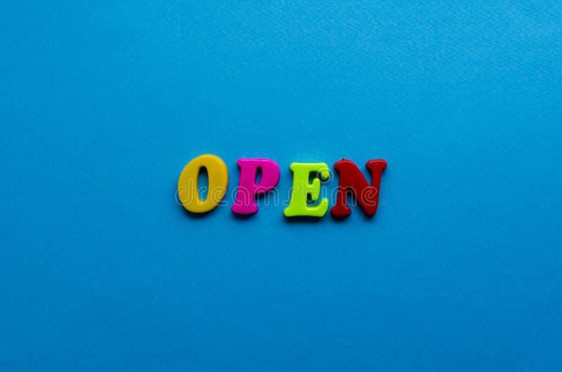 Texte ouvert des lettres colorées en plastique sur le fond de papier bleu photo stock