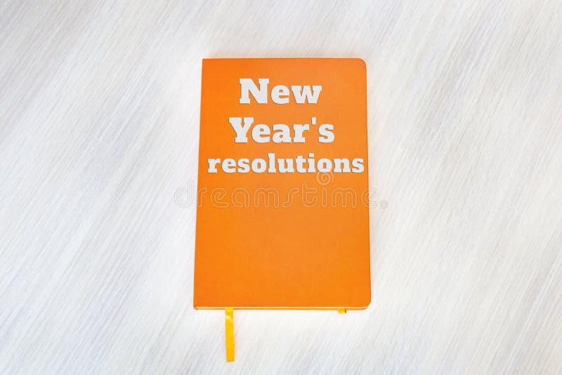 Texte : Résolutions du ` s de nouvelle année concernant la couverture du livre orange sur photographie stock