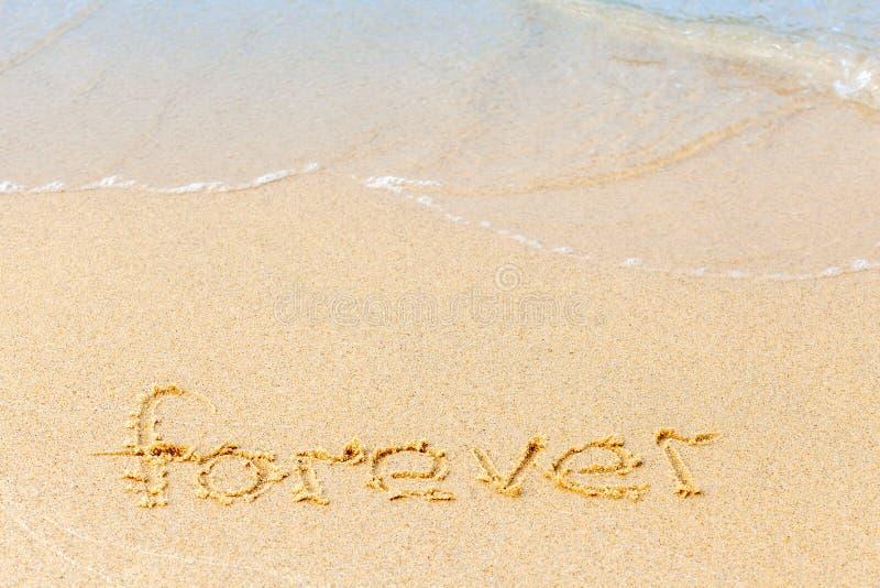 Texte sur une plage ensoleillée Le mot Forever écrit à la main dans le sable, emporté par la vague de la mer Le concept d'ironie photographie stock