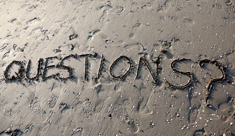 TextFRÅGOR med frågefläcken som är skriftlig på sanden, kan vara bruk fotografering för bildbyråer