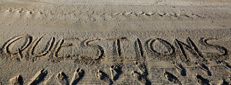 TextFRÅGOR på sanden av stranden arkivfoto
