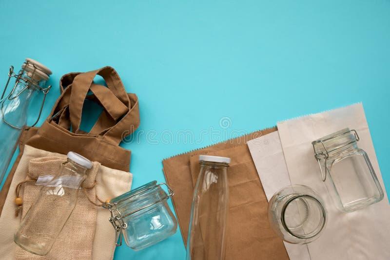 Textielecozakken, document pakketten en glaskruiken die op blauwe achtergrond liggen Vriendschappelijke Eco, hergebruik of nul af royalty-vrije stock afbeelding