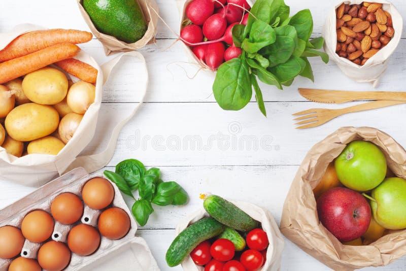 Textil och pappers- påsar med grönsaker och frukter och återvinningsbar bambuköksgeråd Nollshopping för förlorad mat, ecovänskaps royaltyfri foto