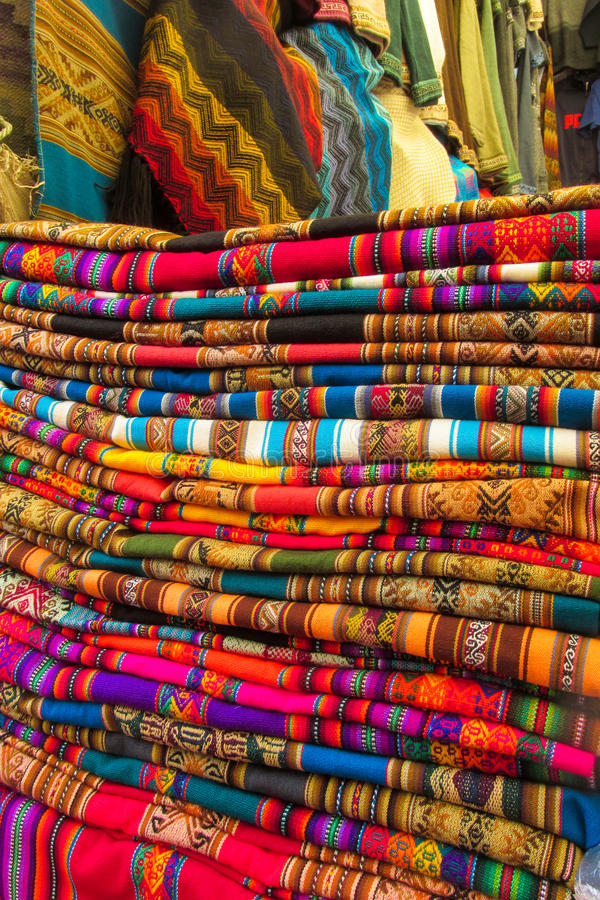 Textil in Peru. Traditional covers, scarf shop. Red, yellow, blue, green, violet colour covers lie in a stack royalty free stock image