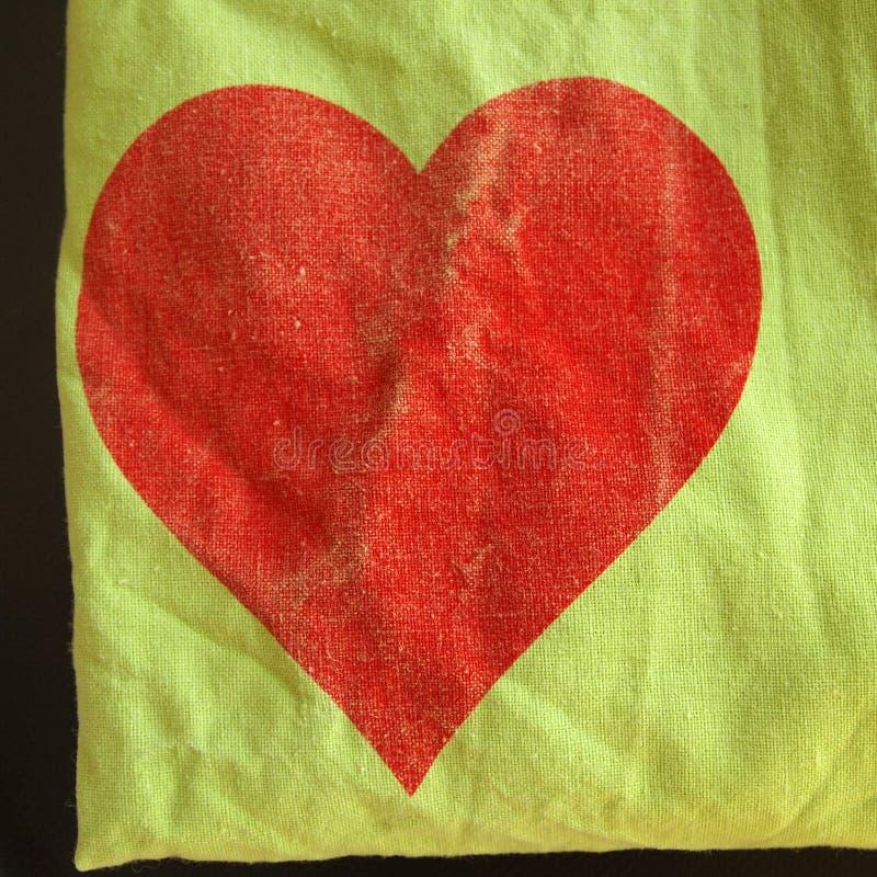 Textilbakgrund med röd hjärta arkivbilder