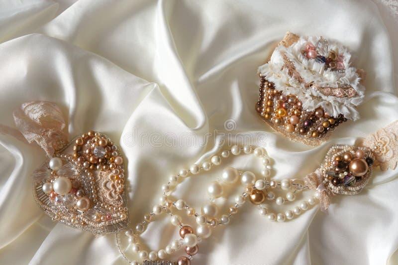 Textilbröllopbakgrund med handen - gjorda brud- smycken arkivbild