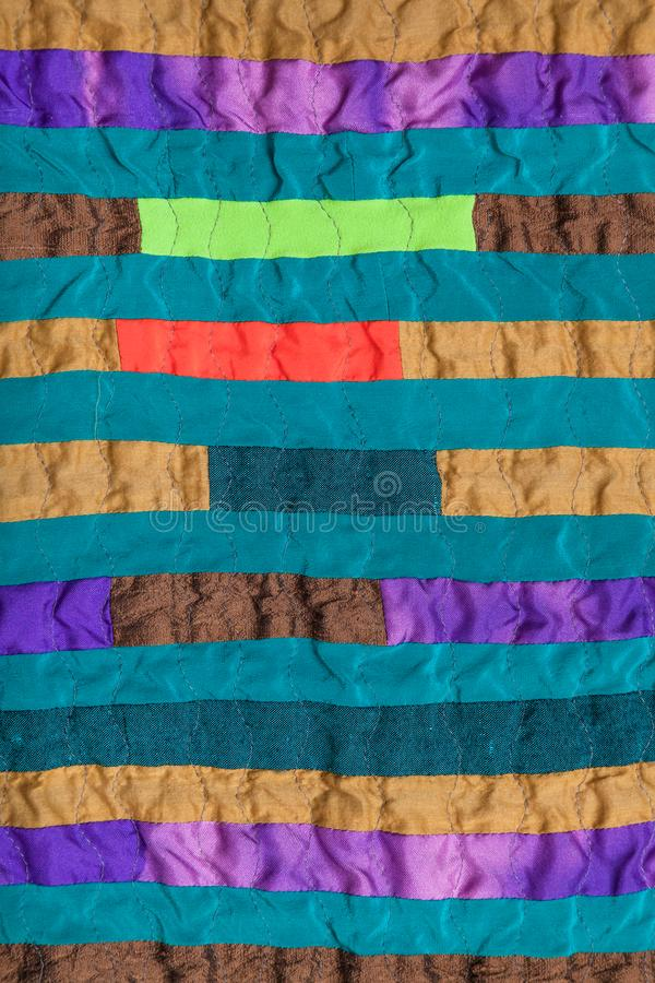 Stitched patchwork scarf from many narrow bands stock photo