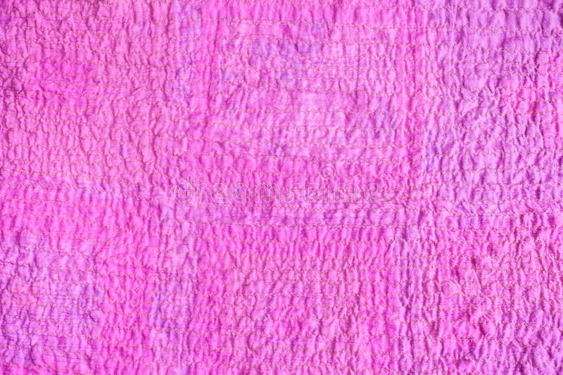 Surface of scarf stitched from crushed pink fabric. Textile background - surface of scarf stitched from crushed pink cotton fabric royalty free stock image