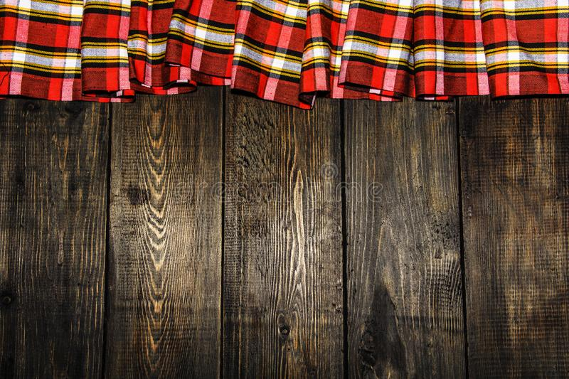 Textile in a cage and wood texture. Black wooden table. Cloth in a cage on a black wooden texture. Colorful fabric on the table. V royalty free stock photos