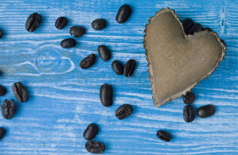 Textile coffee-colored heart on a turquoise wooden background. Valentine`s day concept stock photography