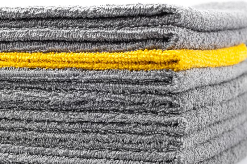 Stack of gray and yellow terry towels, conceptual. Background, close-up stock images