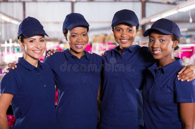Textile factory co-workers. Portrait of beautiful young textile factory co-workers stock photo