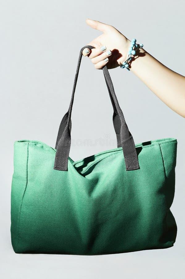 Textile handbag in woman hand. fashion green sport bag. Textile handbag in beautiful woman hand. fashion green sport bag stock photo