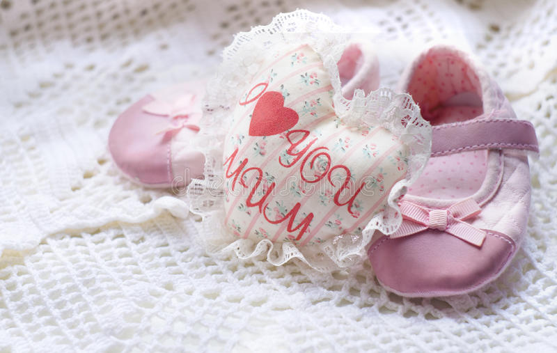 Textile handmade white heart with the inscription I love mum and little pink baby shoes on a white knitted napkin royalty free stock photography