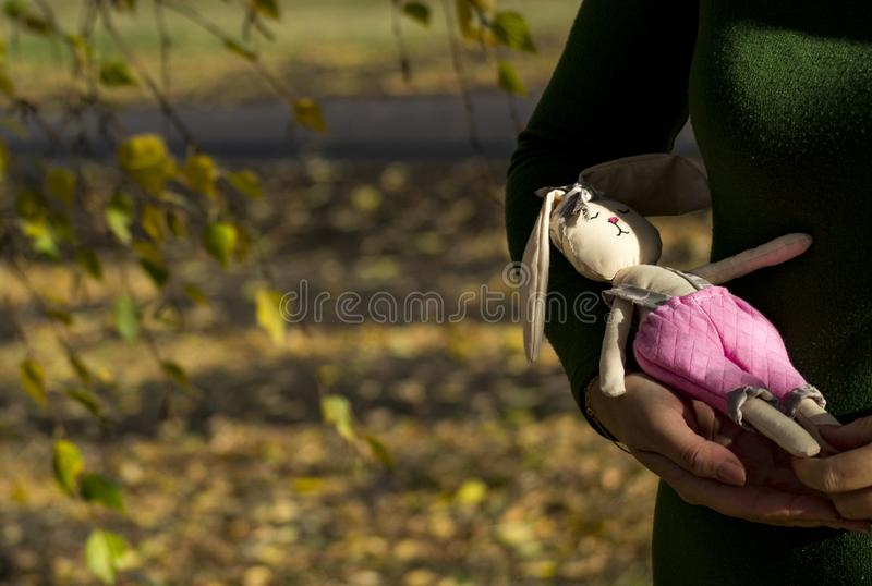 Textile hare toy in multi-colored clothes lying on a woman`s hand. Registration of holidays. Interior fairy doll royalty free stock photography