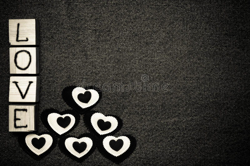 Textile heart, inscription LOVE on wooden cubes and space for text. Romantic love theme on jeans background. Toned.  stock images