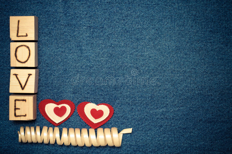 Textile heart, inscription LOVE on wooden cubes and space for text. Romantic love theme on jeans background. Toned.  stock photos