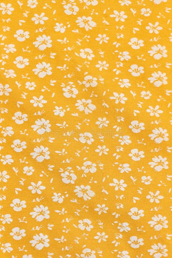 Textile wallpaper in floral print. Yellow fabric background in small white flowers. Small white flowers seamless pattern royalty free stock images