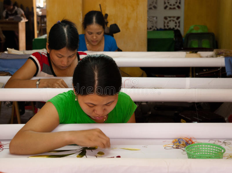 Textile workers in a small asian factory royalty free stock image