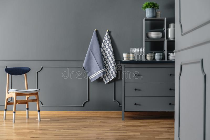Textiles in grey kitchen interior. Wooden chair against grey wall with molding and textiles in kitchen interior with cabinet royalty free stock photos