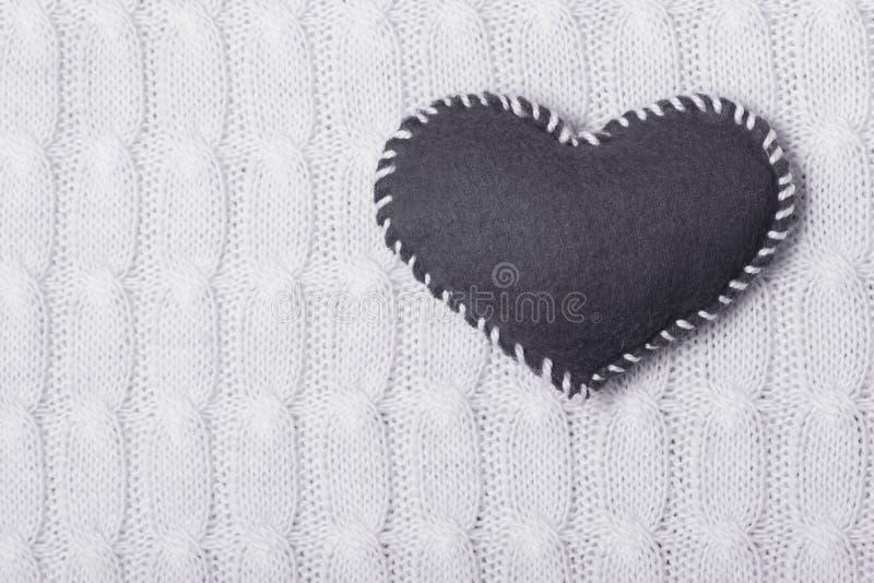 Textilhjärta på en stucken textur arkivbilder