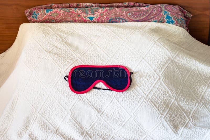 textilsömnmaskering på säng arkivfoto