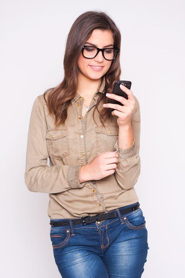 texting在她的在白色背景的手机的妇女 免版税图库摄影