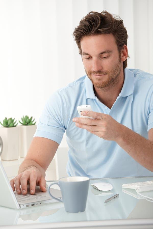 texting在移动电话的微笑的人 库存照片