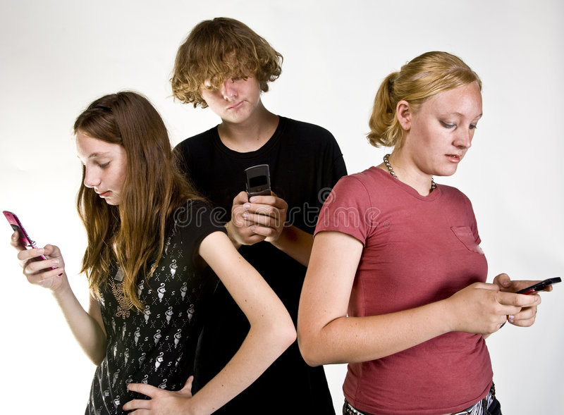 texting移动电话的十几岁 免版税库存照片