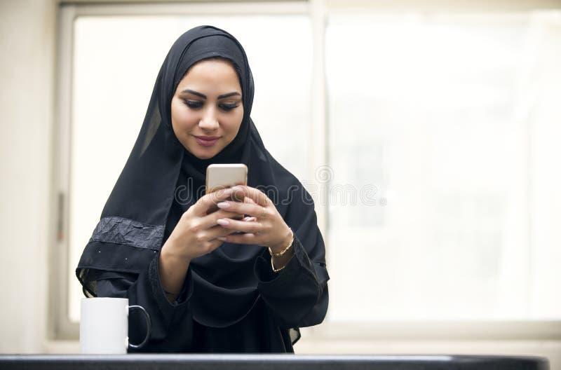 Texting árabe novo bonito da mulher fotografia de stock