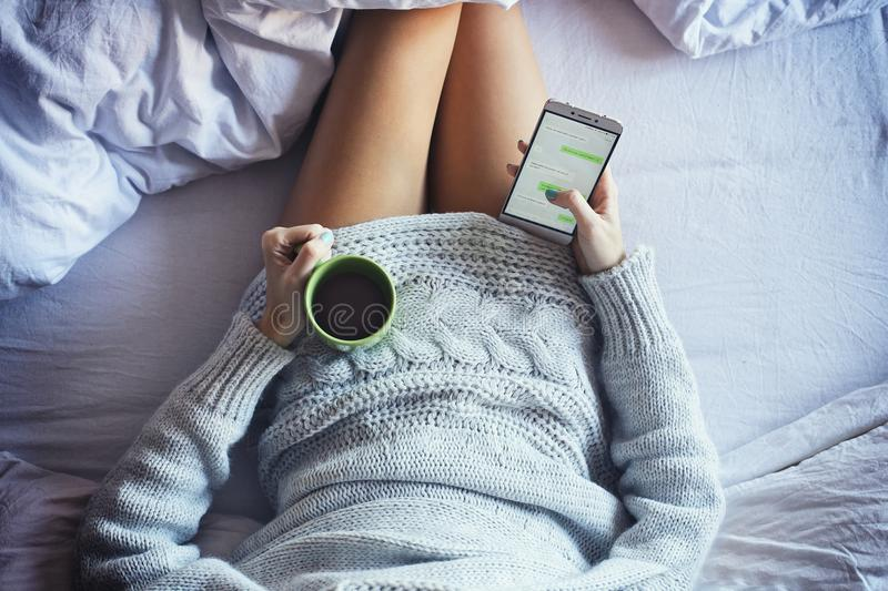 Texting in bed royalty free stock photo