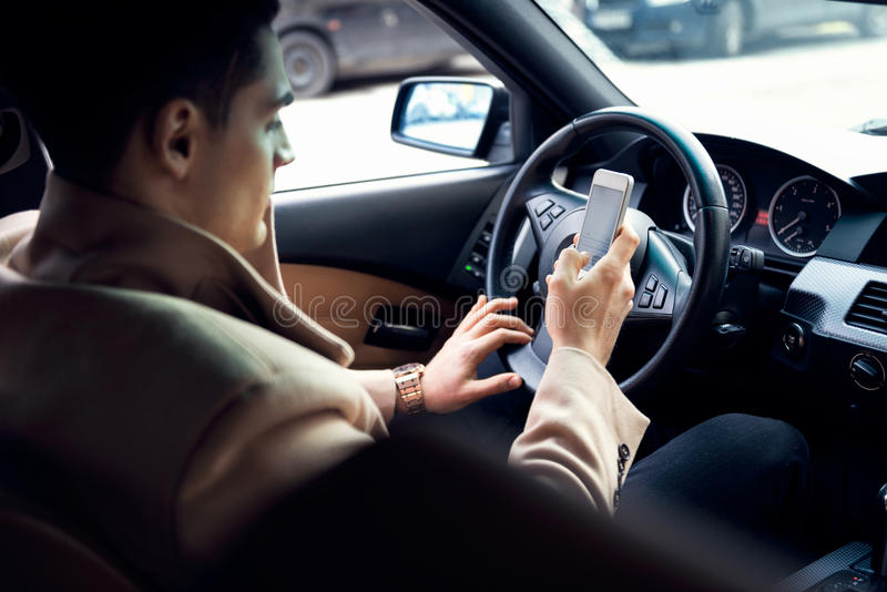 Texting in de auto stock afbeeldingen