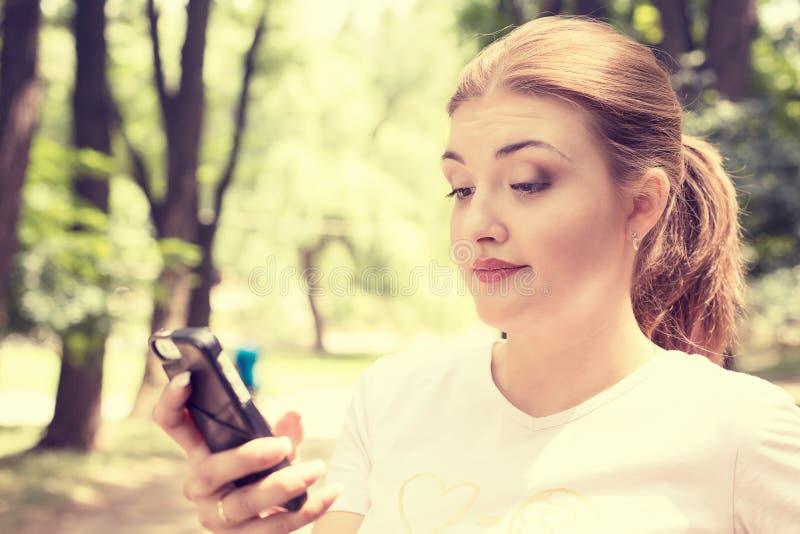 Texting de fala da mulher séria infeliz cética virada no telefone imagem de stock
