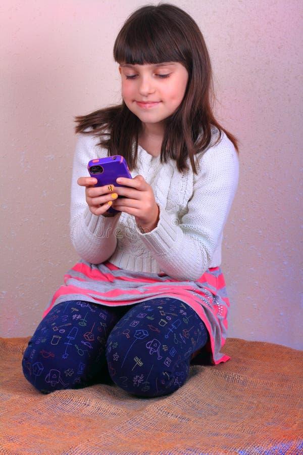 Texting de sorriso da menina do Preteen foto de stock royalty free