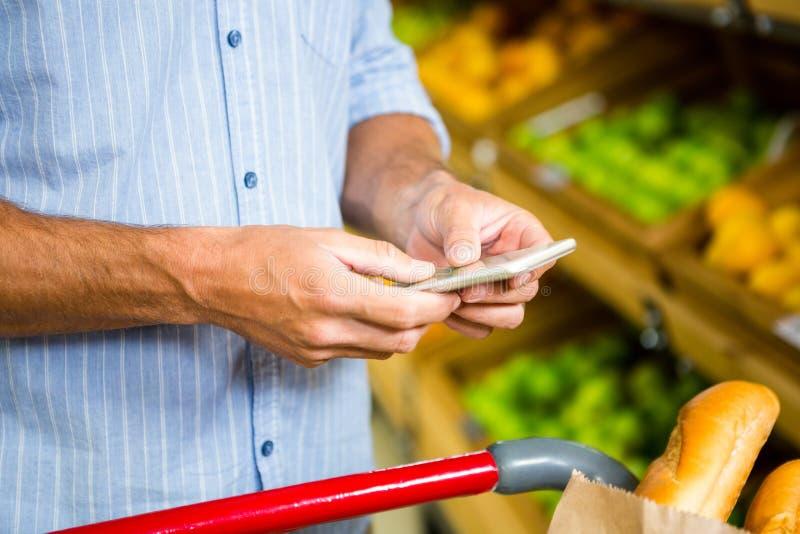 Texting e compras na mercearia do homem imagens de stock royalty free