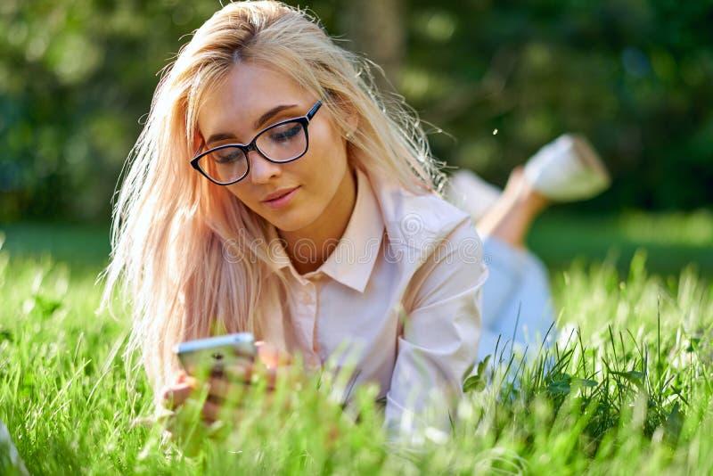 Texting fêmea dos jovens felizes atrativos em seu telefone celular fora da colocação na grama foto de stock