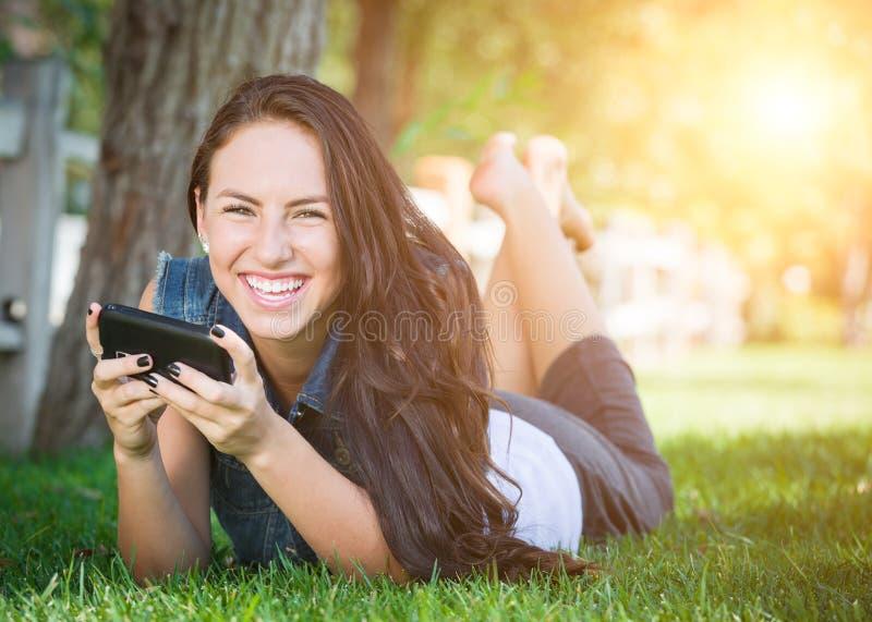 Texting fêmea novo da raça misturada no telefone celular fora no Gra foto de stock royalty free