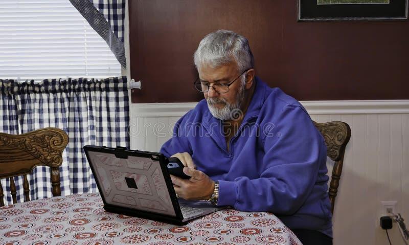 Texting feliz do idoso em seu telefone imagens de stock royalty free