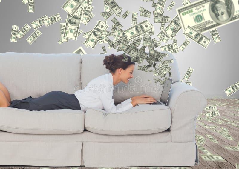 texting geld Gelukkige jonge vrouw op de bank met laptop Geld die omhoog uit laptop komen royalty-vrije stock afbeeldingen
