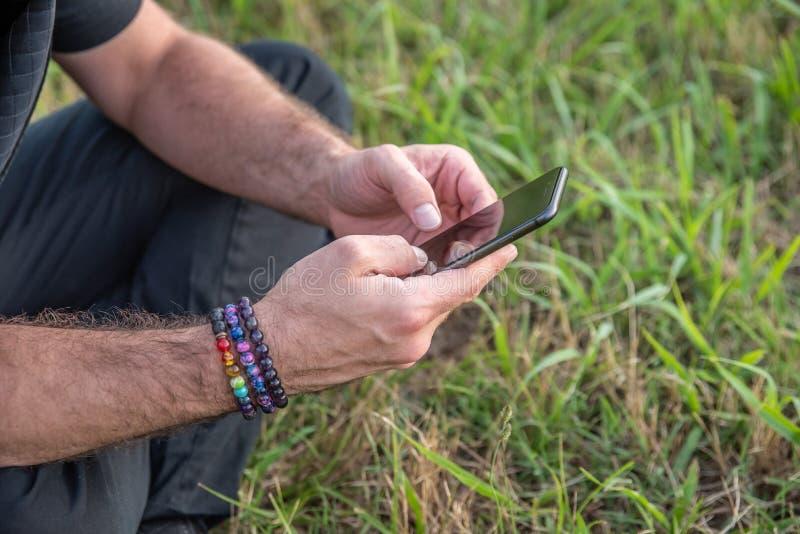 Texting masculino caucasiano na pilha, sentando-se na parte externa da grama com braceletes do arco-íris fotografia de stock royalty free