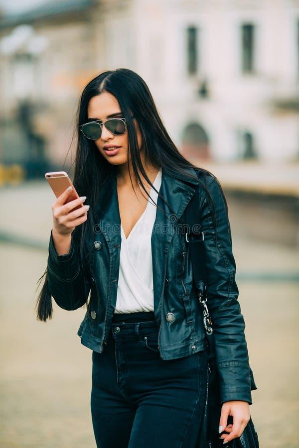 Texting ocasional bonito novo da mulher/que chama seu telefone celular foto de stock royalty free