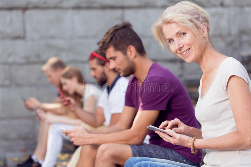 Texting to friend. Pretty young women with smartphone sitting next to people texting to friend royalty free stock image