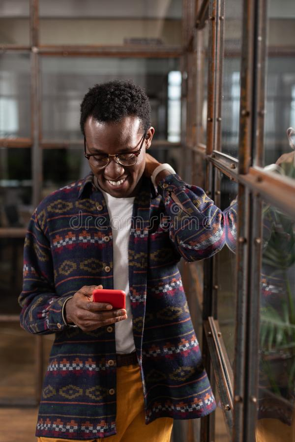 Smiling man receiving good news while texting royalty free stock photo