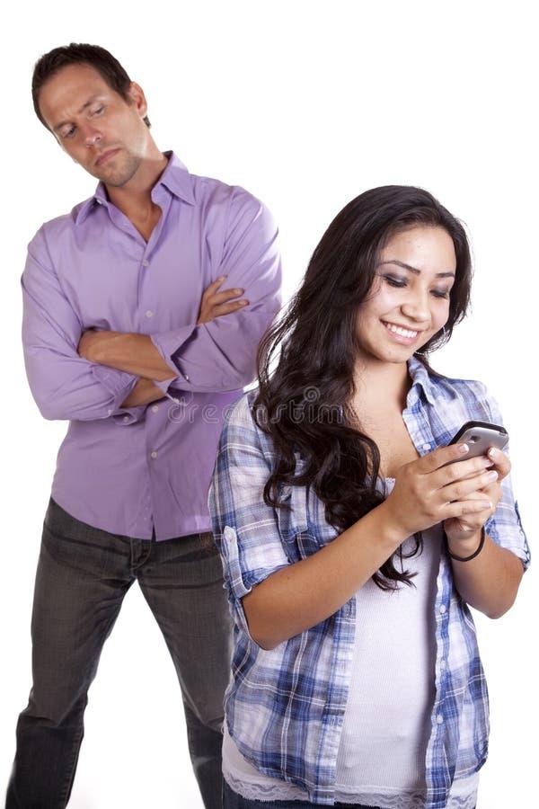Texting y hombre detrás de la observación imagen de archivo libre de regalías