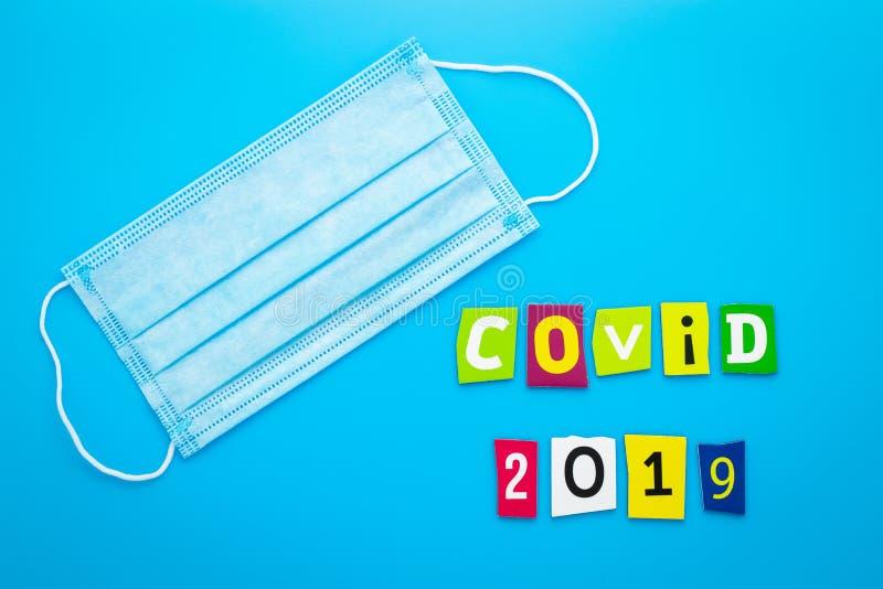 Texto Covid-2019 Coronavirus Mascarillas médicas sobre fondo azul Máscara respiratoria para la protección frente a virus Título,  fotos de archivo