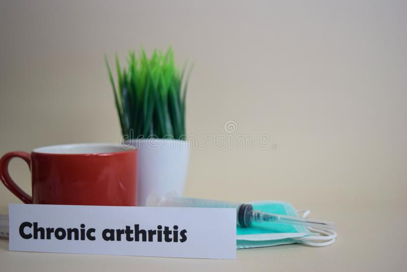Texto crônico da artrite, potenciômetro da grama, copo de café, seringa, e máscara verde da cara imagens de stock royalty free