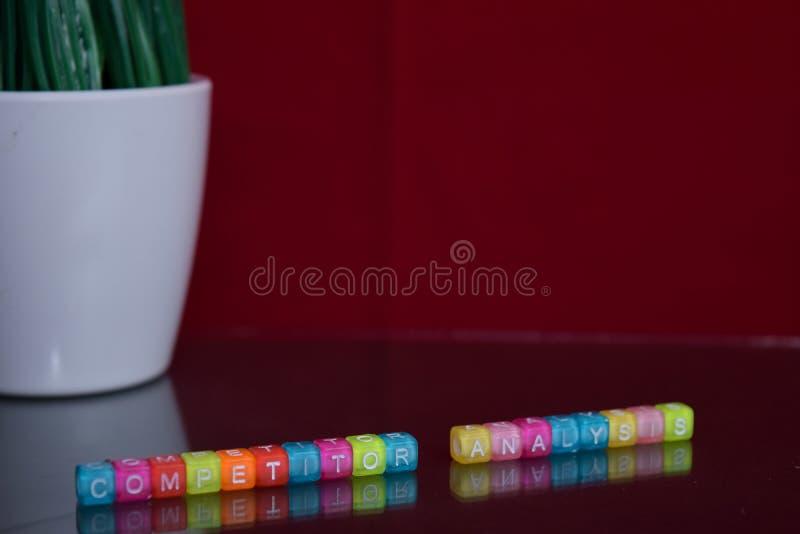 Texto da análise do concorrente no bloco de madeira colorido no fundo vermelho Escritório da mesa e conceito da educação imagem de stock royalty free