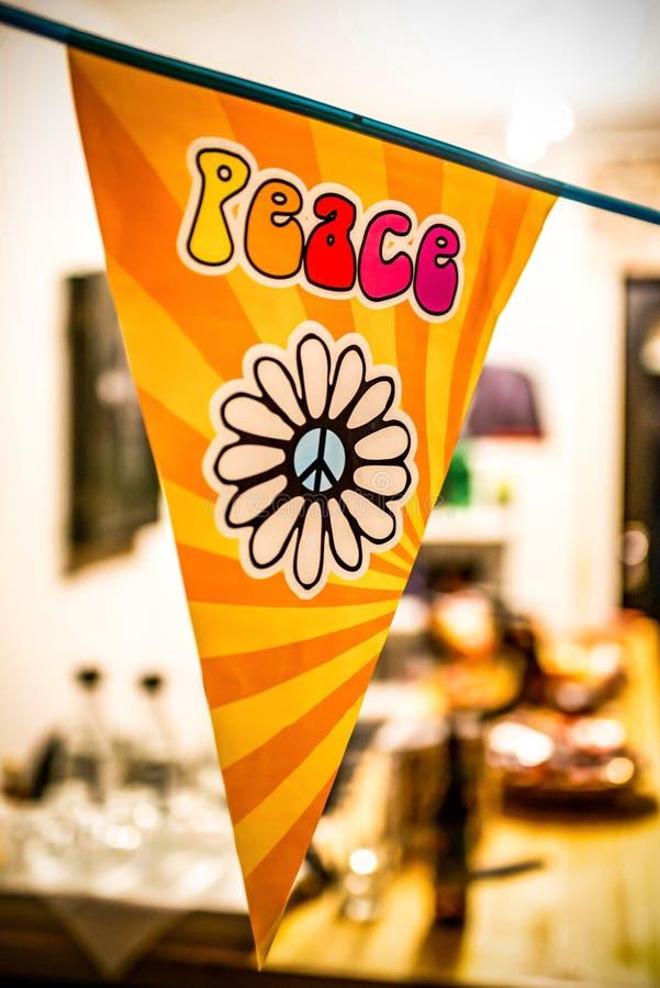 Texto da paz da hippie e camionete de flower power do amor em um sinal de suspensão do partido sobre um fundo borrado fotos de stock