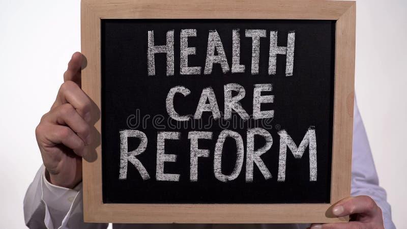 Texto da reforma dos cuidados médicos no quadro-negro nas mãos do doutor, política do governo estadual fotografia de stock royalty free