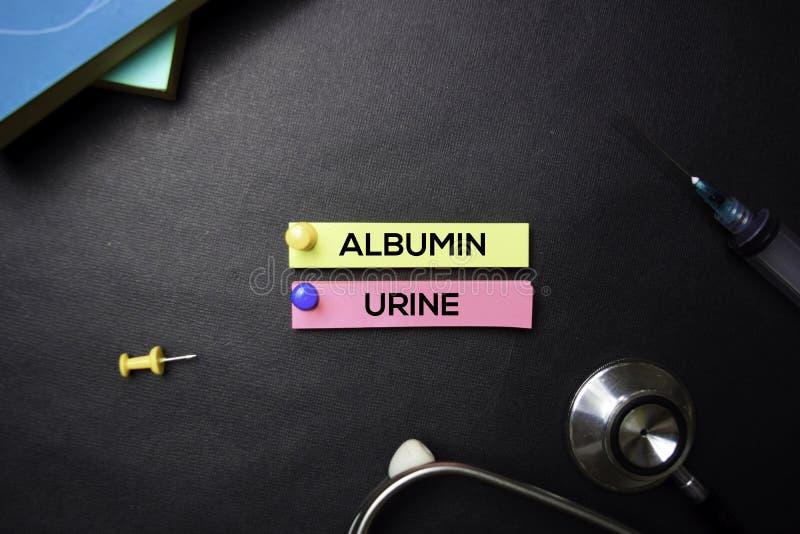 Texto da urina da albumina em notas pegajosas Vista superior isolada no fundo preto Cuidados m?dicos/conceito m?dico fotos de stock